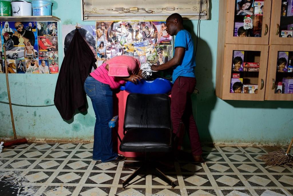 Een kapper wast het haar van een klant